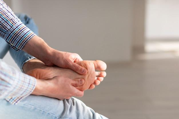 불편한 신발로 인해 오랫동안 걷는 후 통증을 완화하기 위해 발 마사지를 자신에게주는 남자 손.