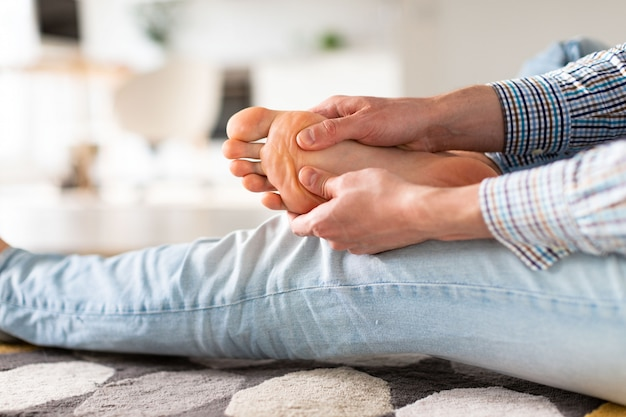 Man hands giving foot massage to yourself to relieve pain after a long walk, due to uncomfortable shoes, suffering from flat feet