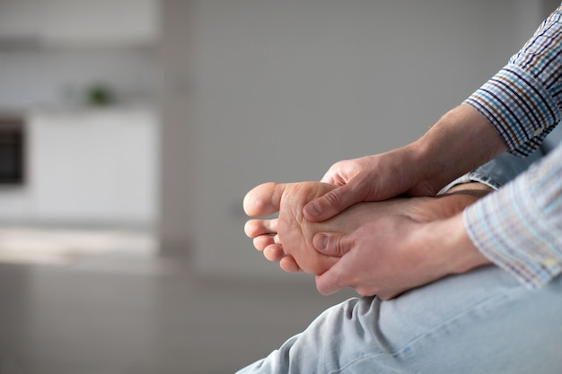 Man hands giving foot massage to yourself to relieve pain after a long walk, due to uncomfortable shoes.