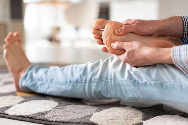 Man hands giving foot massage to yourself to relieve pain after a long walk. flat feet, leg fatigue.