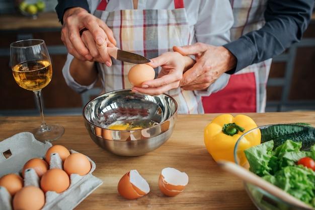 男の手がナイフで卵を割る女性を助ける