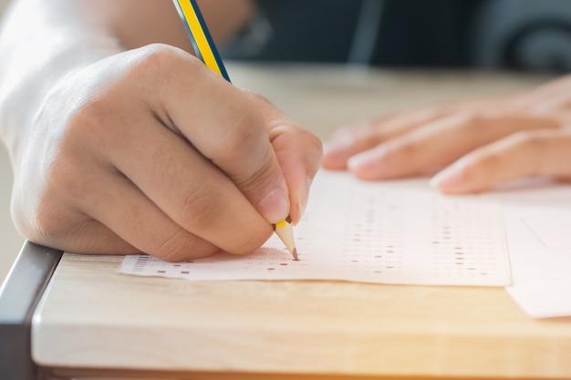 男の手高校、試験のための鉛筆を保持している大学生の答え