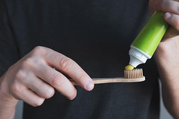 男の手は緑の歯磨き粉で竹の歯ブラシを保持します。歯科衛生