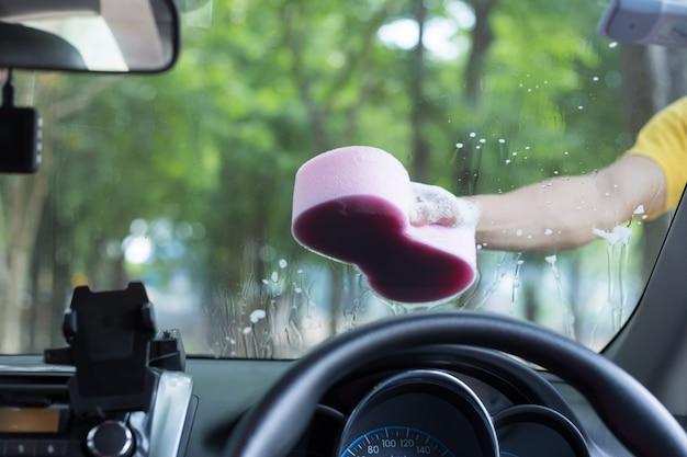 Мужские руки держат губку для мытья белой машины