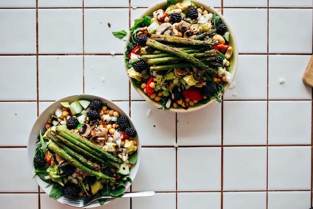 新鮮な有機生物成分、野菜や果物、ベリー、その他の栄養物から作られた健康的な古菜食主義のサラダでいっぱいの大きな深いプレートを持っている男の手