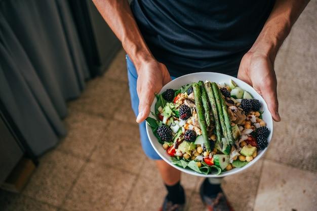 健康的な古菜食主義のサラダでいっぱいの大きな深いプレートを持っている男の手