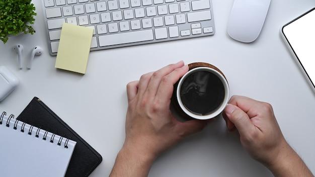 白いテーブルの上のコーヒーカップを保持している男の手。