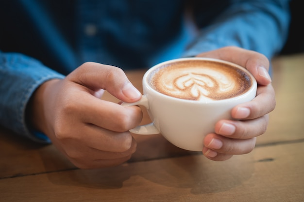 Man hands holding a cup of coffee on wooden table