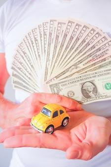 Человек руки, держа долларовых купюр и желтый автомобиль