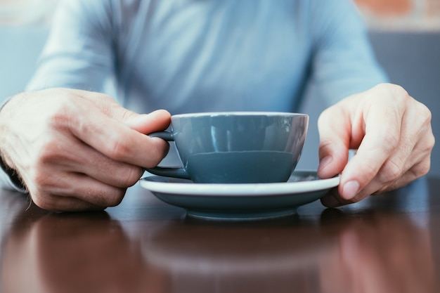 Man hands holding a mug. coffee cappuccino hot chocolate latte or tea in a cup.