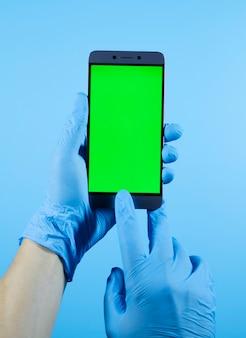 Человек руки держит телефон в защитной медицинской перчатке, вирус коронавируса covid-19