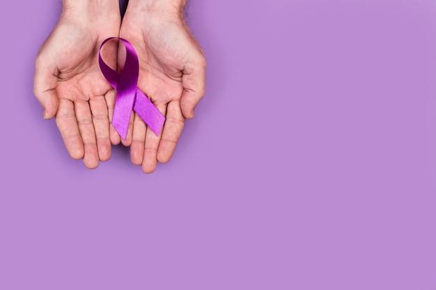 Man hands holding a purple ribbon on purple
