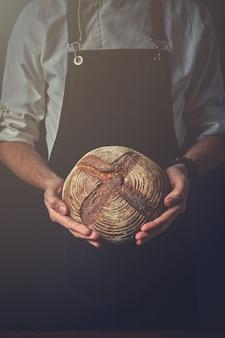 Man hands holding round dark bread, blurred background