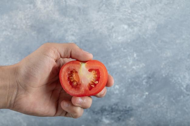 赤いトマトのスライスを保持している男の手。高品質の写真