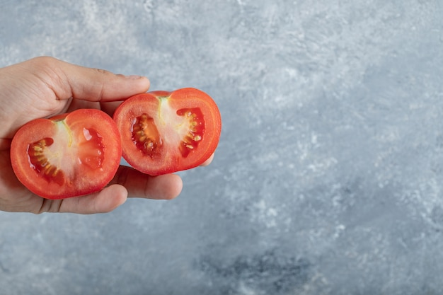 赤いトマトのスライスを持っている男の手。高品質の写真