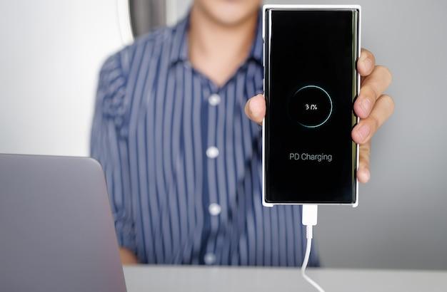 Человек руки держит смартфон, заряжающий аккумулятор от порта типа c ноутбука с использованием технологии зарядки pd
