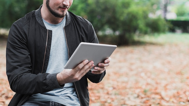 Man hands holding a tablet in park