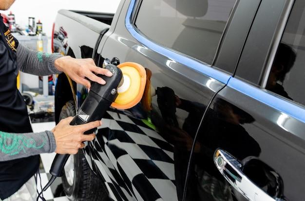 作業工具を持っている男の手が車を磨く