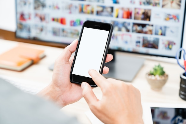 Man hands holding touching mobile smartphone blank white screen for mock up and app design