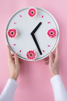Man hands holding white clock created from fresh pink gerbera flowers