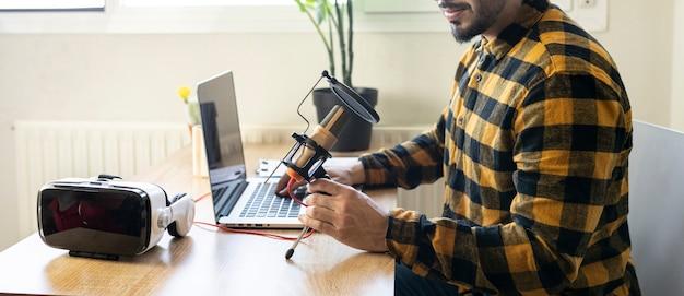 コンピューターを使用している間、彼の手でマイクを持ってオフィスで手