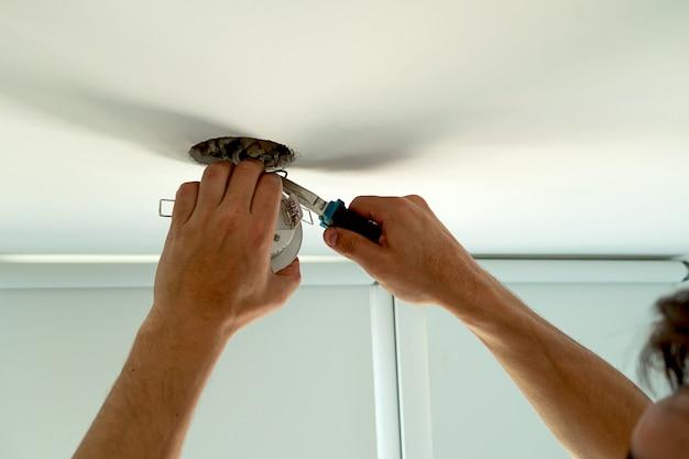 전구 소켓을 설치하는 남자 손. 흰색 방에 있는 천장 조명 실내 주택을 수리합니다.