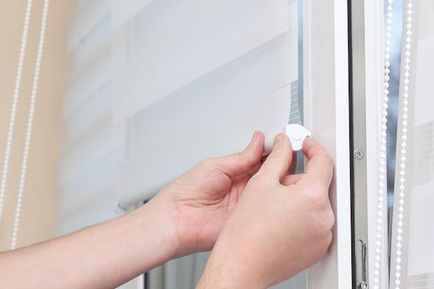남자 손 설치 창 롤러 듀오 시스템 낮과 밤.