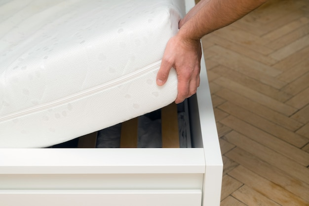 Man hands lifting the mattress at the bedroom.