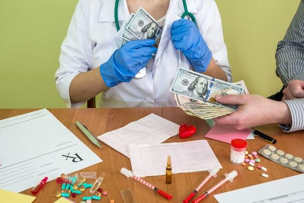 男の手は医者にユーロのお金を支払う