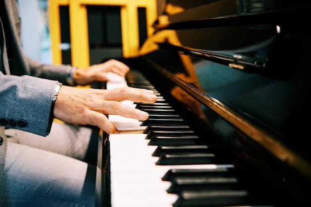 Человек руки играет на пианино