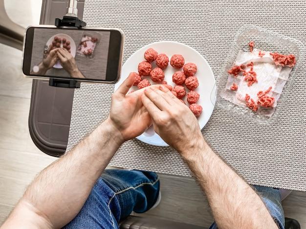 스마트 폰에 원시 다진 고기 녹화 비디오와 미트볼을 준비하는 사람 손. 라이프 스타일은 자연 채광으로 구성을 닫습니다. 수제 요리 블로거 인플 루 언서 스트리밍 블로깅 개념
