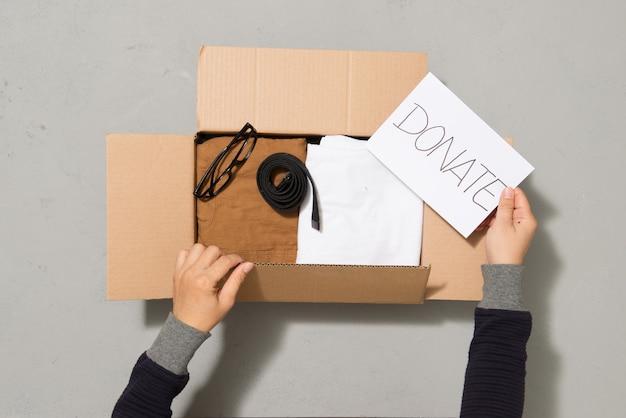 箱を寄付するために服を置く男の手
