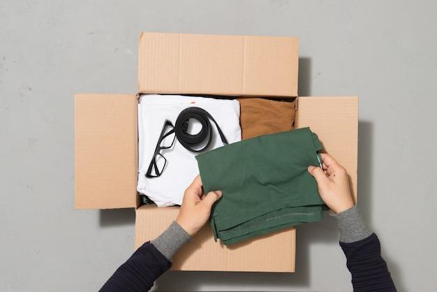 Человек руки положить одежду, чтобы пожертвовать коробку