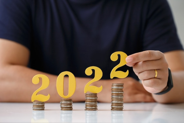 Man hands putting gold wooden number 2022 on stack of coins tax payment investment and banking022 n