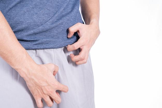 Руки человека почесывая его промежность изолированный белый фон. медицина, здравоохранение для рекламной концепции.