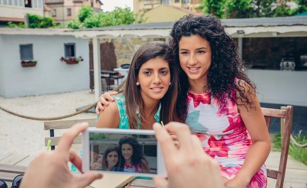 夏の日に屋外に座っている2人の笑顔の若い女性にスマートフォンで写真を撮る男の手