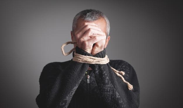 Руки человека связаны веревкой. тюремное заключение