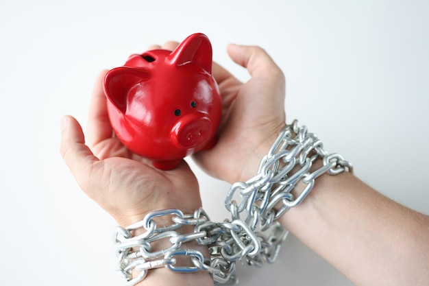 In man hands tied by chain red pig piggy bank credit addiction concept