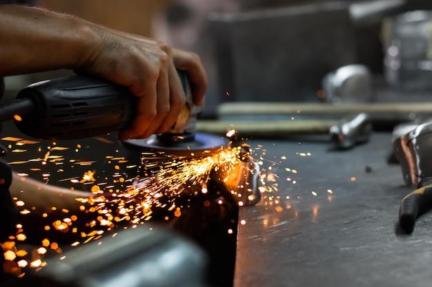 Руки человека обработки металлических частей оборудования в мастерской с угловой шлифовальной машиной. мужчина-слесарь полирует и дорабатывает средневековый доспех.