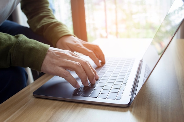 Man hands typing on laptop or computer