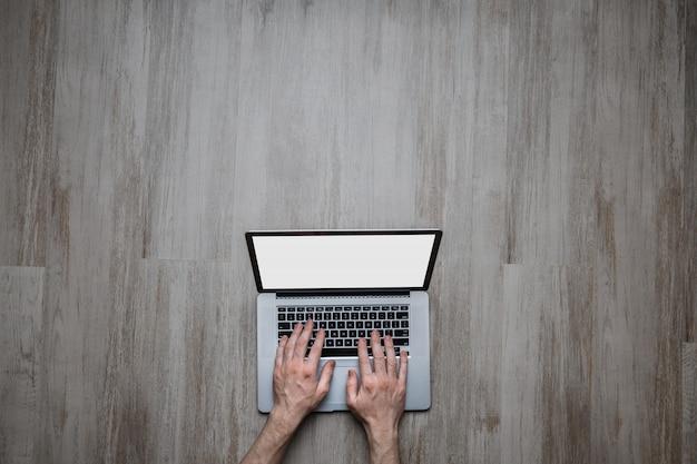Man hands typing on laptop keyboard on empty gray wooden desk