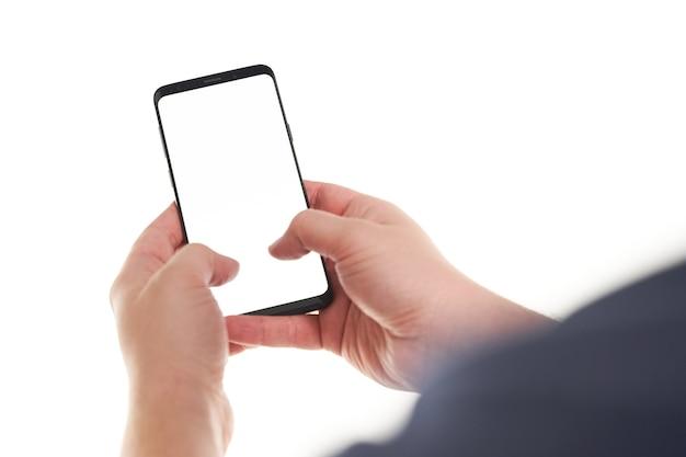 白い背景で隔離のモダンなフレームレスデザインで黒いスマートフォンの空白の画面で入力する男の手