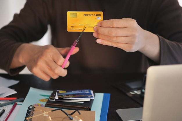 Человек руки используют ножницы, чтобы сократить кредитные карты, концепция для погашения долгов, прекратить использование кредитных карт на рабочем столе, сосредоточиться на кредитной карте мелкой dof
