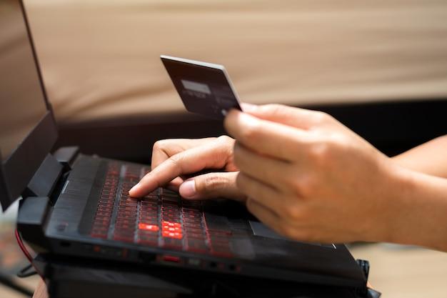 ラップトップコンピューターを使用し、クレジットカードを保持している男の手。オンラインショッピングとオンライン支払いの概念。