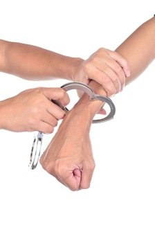 Man hands with handcuffs got arrested isolated on white background
