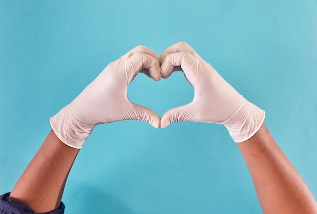 Человек руки с латексными перчатками, образуя сердце.