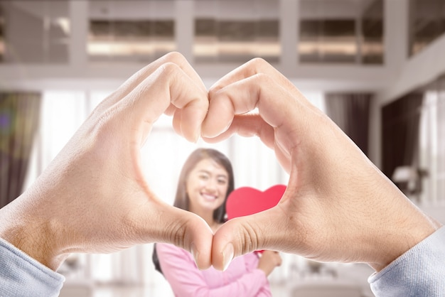 Man hands with the shape of the heart showing his girlfriend holding a red heart