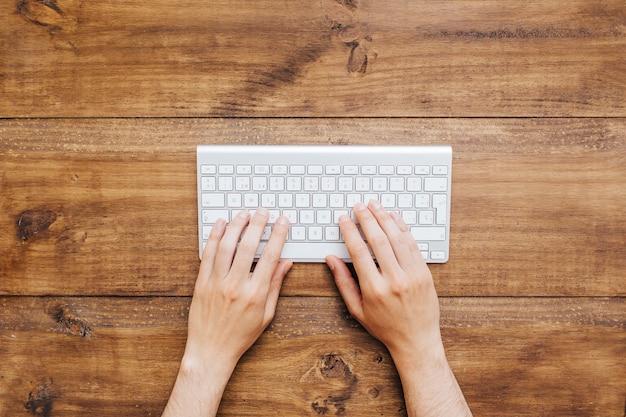 Человек руками работает на клавиатуре над деревянным фоном