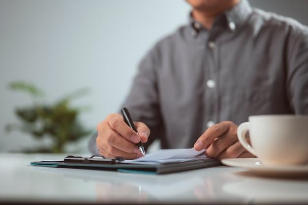 Человек руки писать в буфер обмена ручкой белый на столе