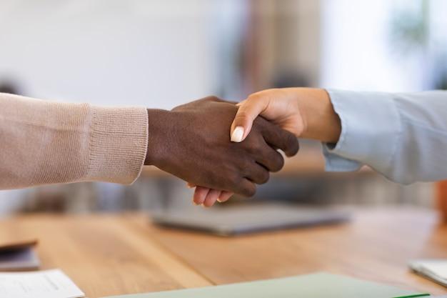 彼の新しいオフィスの仕事のために受け入れられた後、彼の雇用主を握手する男